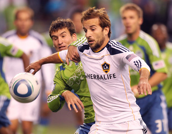 SEATTLE - OCTOBER 31:  Mike Magee #18 of the Los Angeles Galaxy battles Nathan Sturgis #12 of the Seattle Sounders FC during the 1st leg playoff game at Qwest Field on October 31, 2010 in Seattle, Washington. The Galaxy defeated the Sounders 1-0. (Photo b