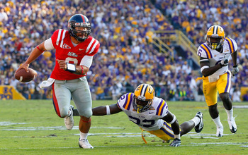 BATON ROUGE, LA - NOVEMBER 20:  Quarterback Jeremiah Masoli #8 of the Ole Miss Rebels breaks away from Ryan Baker #22 and Craig Loston #6 of the Louisiana State University Tigers at Tiger Stadium on November 20, 2010 in Baton Rouge, Louisiana.  (Photo by