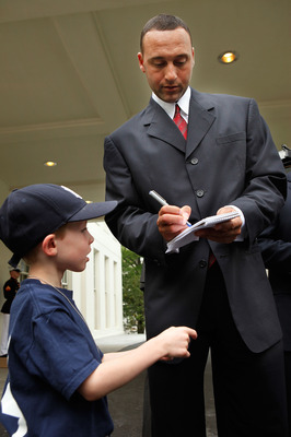 WASHINGTON - APRIL 26:  World Series champion New York Yankees player Derek Jeter (R) gives an autograph to six-year-old David Williamson, son of Wall Street Journal reporter Elizabeth Williamson, outside the West Wing of the White House April 26, 2010 in