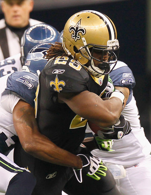 NEW ORLEANS - NOVEMBER 21:  Chris Ivory #29 of the New Orleans Saints is tackled by Lawyer Milloy #36 of the Seattle Seahawks at Louisiana Superdome on November 21, 2010 in New Orleans, Louisiana.  (Photo by Kevin C. Cox/Getty Images)