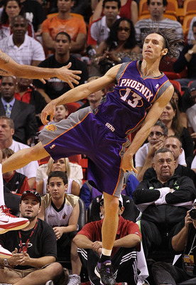 MIAMI - NOVEMBER 17:  Steve Nash #13  of the Phoenix Suns passes the ball around Eddie House #55 during a game against the  Miami Heat at American Airlines Arena on November 17, 2010 in Miami, Florida. NOTE TO USER: User expressly acknowledges and agrees