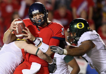 TUCSON, AZ - NOVEMBER 21:  Quarterback Nick Foles #8 of the Arizona Wildcats is sacked by Blake Ferras #90 and Will Tukuafu #39 of the Oregon Ducks during the college football game at Arizona Stadium on November 21, 2009 in Tucson, Arizona. The Ducks defe