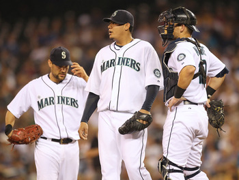 SEATTLE - AUGUST 05:  Starting pitcher Felix Hernandez #34 of the Seattle Mariners pauses just before being removed from the game as first baseman Casey Kotchman #13 and catcher Adam Moore #10 look on in the seventh inning against the Texas Rangers at Saf