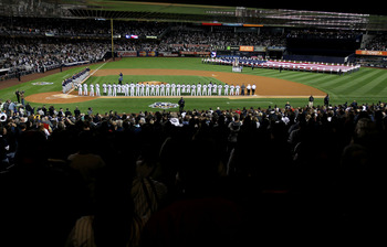 NEW YORK - OCTOBER 09:  The New York Yankees and the Minnesota Twins stand for the performance of the National Anthem during Game Three of the ALDS part of the 2010 MLB Playoffs at Yankee Stadium on October 9, 2010 in the Bronx borough of New York City.