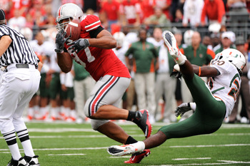 COLUMBUS, OH - SEPTEMBER 11:  Cameron Heyward #97 of the Ohio State Buckeyes steps in front of Damien Berry #20 of the Miami Hurricanes to intercept a pass at Ohio Stadium on September 11, 2010 in Columbus, Ohio. Ohio State intercepted Miami four times en