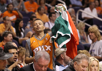 PHOENIX - MAY 05:  A Phoenix Suns fan holds up a Mexican flag as he cheers during Game Two of the Western Conference Semifinals of the 2010 NBA Playoffs against the San Antonio Spurs at US Airways Center on May 5, 2010 in Phoenix, Arizona. The team is wea