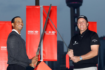 SHANGHAI, CHINA - NOVEMBER 02:  Tiger Woods of the USA (L) and Phil Mickelson of the USA cross swords during the 2010 WGC-HSBC Champions Photocall at The Peninsula hotel on The Bund, Shanghai on November 2, 2010 in Shanghai, China.  (Photo by Ross Kinnair
