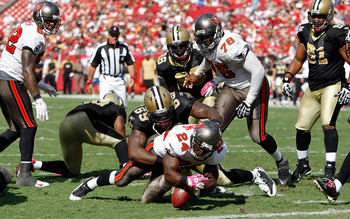 TAMPA, FL - OCTOBER 17:  Running back Carnell Williams #24 of the Tampa Bay Buccaneers is stopped just short of the goal line by defensive lineman Anthony Hargrove #69 of the New Orleans Saints during the game at Raymond James Stadium on October 17, 2010