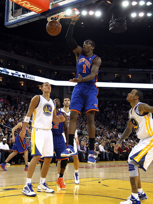 OAKLAND, CA - NOVEMBER 19:  Amar'e Stoudemire #1 of the New York Knicks dunks the ball over Andris Biedrins #15 of the Golden State Warriors at Oracle Arena on November 19, 2010 in Oakland, California. NOTE TO USER: User expressly acknowledges and agrees