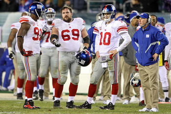 PHILADELPHIA - NOVEMBER 21:  Justin Tuck #91, Rich Seubert #69, Eli Manning #10 and head coach Tom Coughlin of the New York Giants look on during a challenge on a fumble by Manning late in the fourth quarter against the Philadelphia Eagles at Lincoln Fina