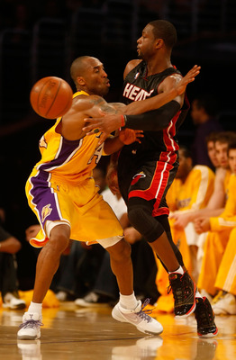 LOS ANGELES, CA - DECEMBER 04:  Dwayne Wade #3 of the Miami Heat passes the ball while being defended by Kobe Bryant #24 of the Los Angeles Lakers in the second half at Staples Center on December 4, 2009 in Los Angeles, California. The Lakers defeated the