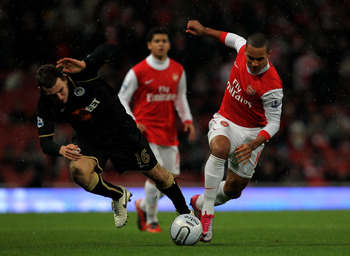LONDON, ENGLAND - NOVEMBER 30:  Theo Walcott (R) of Arsenal in action against James McCarthur of Wigan as Denilson of Arsenal looks on during the Carling Cup quarter final match between Arsenal and Wigan Athletic at the Emirates Stadium on November 30, 20