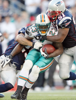 FOXBORO, MA - NOVEMBER 08:  Ronnie Brown #23 of the Miami Dolphins is stopped by Pat Chung #25 and Jerod Mayo #51 of the New England Patriots on November 8, 2009 at Gillette Stadium in Foxboro, Massachusetts. The Patriots defeated the Dolphins 27-17.  (Ph