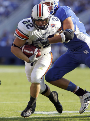 LEXINGTON, KY - NOVEMBER 5:   Tre Smith #23 of the Auburn Tigers runs with the ball while dragging a   Kentucky Wildcats with him on November  5, 2005 at Commonwealth Stadium in Lexington, Kentucky.  (Photo by Andy Lyons/Getty Images)