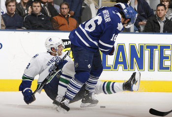 TORONTO - NOVEMBER 13: Clarke MacArthur #16 of the Toronto Maple Leafs runs into Alexander Edler #23 of the Vancouver Canucks during game action at the Air Canada Centre November 13, 2010 in Toronto, Ontario, Canada. (Photo by Abelimages / Getty Images)