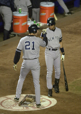 25 Oct 2000:  Outfielder Paul O''Neill #21 of the New York Yankees is congratulated by Derek Jeter #2 after scoring on a Scott Brosius sacrifice in the second inning against the New York Mets during Game 4 of the World Series at Shea Stadium in Flushing,