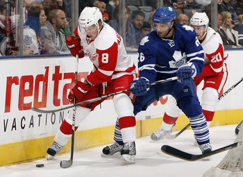 TORONTO - OCTOBER 2: Mike Zigomanis #26 of the Toronto Maple Leafs hooks Justin Abdelkader #8 of the Detroit Red Wings during a preseason NHL game at the Air Canada Centre October 2, 2010 in Toronto, Ontario, Canada. (Photo by Abelimages/Getty Images)