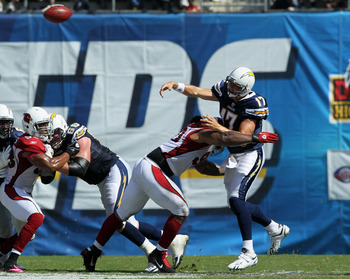 SAN DIEGO - OCTOBER 03:  Quarterback Philip Rivers of the San Diego Chargers throws a pass as he is hit by defensive tackle Darnell Dockett #90 of the Arizona Cardinals at Qualcomm Stadium on October 3, 2010 in San Diego, California.   The Chargers won 41