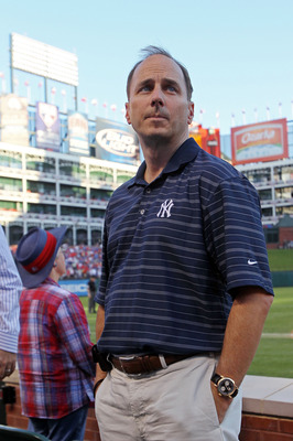 ARLINGTON, TX - OCTOBER 16:  General Manager of the New York Yankees Brian Cashman looks on during a game against the Texas Rangers in Game Two of the ALCS during the 2010 MLB Playoffs at Rangers Ballpark in Arlington on October 16, 2010 in Arlington, Tex