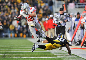 IOWA CITY, IA - NOVEMBER 20: Defenisve back Micah Hyde #18 of the University of Iowa Hawkeyes trips up wide receiver Dane Sanzenbacher #12 of the Ohio State Buckeyes as he drove the ball down field during the first half of play at Kinnick Stadium on Novem