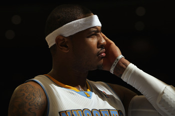 DENVER - NOVEMBER 16:  Carmelo Anthony #15 of the Denver Nuggets looks on during a break in the action against the New York Knicks at the Pepsi Center on November 16, 2010 in Denver, Colorado. The Nuggets defeated the Knicks 120-118. NOTE TO USER: User ex