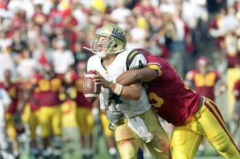 20 Nov 1999: Ryan McCann #4 of the UCLA Bruins is sacked by Lonnie Ford #25 of the USC Trojans at the Los Angeles Memorial Coliseum in Los Angeles, California. The Trojans defeated the Bruins 17-7.