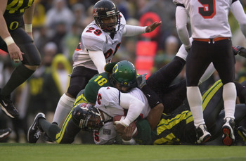 EUGENE, OR - DECEMBER 1:  Tailback Ken Simonton #35 of the Oregon State Beavers is tackled by linebacker Wesley Mallard #18 and safety Marley Tucker #28 of the Oregon Ducks during the game at Autzen Stadium in Eugene Oregon on December 1, 2001.  Oregon de