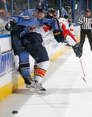 ATLANTA - NOVEMBER 17:  Jim Slater #23 of the Atlanta Thrashers is checked into the boards by Bryan McCabe #24 of the Florida Panthers at Philips Arena on November 17, 2010 in Atlanta, Georgia.  (Photo by Kevin C. Cox/Getty Images)