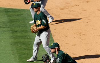 ANAHEIM, CA - SEPTEMBER 29:  First baseman Daric Barton #14, second baseman Mark Ellis #14, and extra infielder Steven Tolleson #30 of the Oakland Athletics fill the right side of the infield as the Los Angeles Angels of Anaheim bat with the bases loaded,