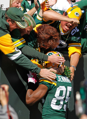 GREEN BAY, WI - OCTOBER 03: Greg Jennings #85 of the Green Bay Packers is grabbed by fans after scoring a first half touchdown against the Detroit Lions at Lambeau Field on October 3, 2010 in Green Bay, Wisconsin. The Packers defeated the Lions 28-26. (Ph