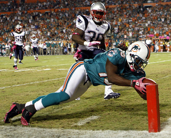MIAMI - OCTOBER 04:  Receiver Davone Bess #15 of the Miami Dolphins scores a touchdown against James Sanders #36 and Devin McCorty #32 of the New England Patriots at Sun Life Stadium on October 4, 2010 in Miami, Florida.  (Photo by Marc Serota/Getty Image