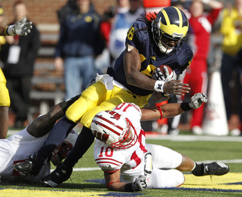 ANN ARBOR, MI - NOVEMBER 20:  Denard Robinson #16 of the Michigan Wolverines dives into the enzone for a fourth quarter touchdown over Devin Smith #10 of the Wisconsin Badgers at Michigan Stadium on November 20, 2010 in Ann Arbor, Michigan. Wisconson won