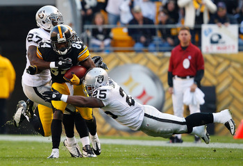 PITTSBURGH - NOVEMBER 21:  Antonio Brown #84 of the Pittsburgh Steelers attempts to run through tackles by Stevie Brown #27 and Rock Cartwright #25 of the Oakland Raiders during the game on November 21, 2010 at Heinz Field in Pittsburgh, Pennsylvania.  (P