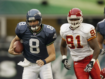 SEATTLE - AUGUST 23:  Quarterback Matt Hasselbeck #8 of the Seattle Seahawks scrambles away from R-Kal Truluck #91 of the Kansas City Chiefs on August 23, 2003 at Seahawks Stadium in Seattle, Washington. The Seahawks defeated the Chiefs 42-31. (Photo by O