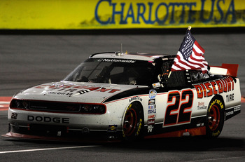 CONCORD, NC - OCTOBER 15:  Brad Keselowski, driver of the #22 Discount Tire Dodge, celebrates by waving the American flag on track after winning the NASCAR Nationwide Series Dollar General 300 at Charlotte Motor Speedway on October 15, 2010 in Concord, No