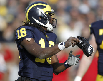 ANN ARBOR, MI - NOVEMBER 20:  Denard Robinson #16 of the Michigan Wolverines puts his shoe back on while playing the Wisconsin Badgers tackles at Michigan Stadium on November 20, 2010 in Ann Arbor, Michigan. Wisconsin won the game 48-38.  (Photo by Gregor