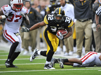 IOWA CITY, IA - OCTOBER 23- Linebacker Kevin Claxton #37 of the Wisconsin Badgers puts pressure on running back Adam Robinson #32 of the University of Iowa Hawkeyes as he rushes for yards during the second half of play at Kinnick Stadium on October 23, 20