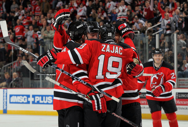 NEWARK, NJ - MARCH 23:  Travis Zajac #19 of the New Jersey Devils celebrates his first goal against the Columbus Blue Jackets with his teammates at the Prudential Center on March 23, 2010 in Newark, New Jersey.  (Photo by Jim McIsaac/Getty Images)
