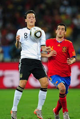 DURBAN, SOUTH AFRICA - JULY 07:  Mesut Oezil of Germany controls the ball on his chest as he is closed down by Sergio Busquets of Spain during the 2010 FIFA World Cup South Africa Semi Final match between Germany and Spain at Durban Stadium on July 7, 201