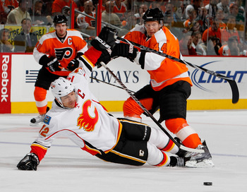 PHILADELPHIA - NOVEMBER 26:  Jarome Iginla #12 of the Calgary Flames is knocked to the ice by Kimmo Timonen #44 of the Philadelphia Flyers during the first period of a hockey game at the Wells Fargo Center on November 26, 2010 in Philadelphia, Pennsylvani