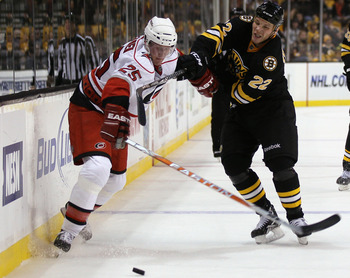 BOSTON - NOVEMBER 26:  Shawn Thornton #22 of the Boston Bruins and Joni Pitkanen #25 of the Carolina Hurricanes fight for the puck on November 26, 2010 at the TD Garden in Boston, Massachusetts. The Hurricanes defeated the Bruins 3-0.  (Photo by Elsa/Gett