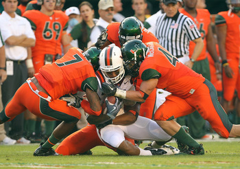 MIAMI - NOVEMBER 20:  Marcus Davis #7 of the Virginia Tech Hokies is hit by Vaughn Telemaque #7 and Colin McCarthy #44 of the Miami Hurricanes at Sun Life Stadium on November 20, 2010 in Miami, Florida.  (Photo by Mike Ehrmann/Getty Images)
