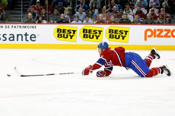 MONTREAL- NOVEMBER 9:  Jeff Halpern #15 of the Montreal Canadiens falls while skating with the puck during the NHL game against the Vancouver Canucks at the Bell Centre on November 9, 2010 in Montreal, Quebec, Canada.  The Canadiens defeated the Canucks 2