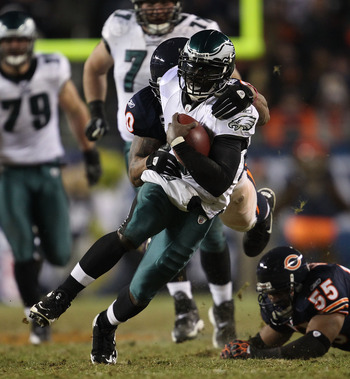 CHICAGO - NOVEMBER 28: Michael Vick #7 of the Philadelphia Eagles is brought down by Julius Peppers #90 of the Chicago Bears after breaking a tackle attempt by Lance Briggs #55 at Soldier Field on November 28, 2010 in Chicago, Illinois. The Bears defeated