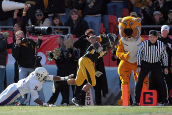 KANSAS CITY, MO - NOVEMBER 27:  Kendial Lawrence #4 of the Missouri Tigers carries the ball across the goal line for a touchdown as Greg Brown #5 of the Kansas Jayhawks defends during the game on November 27, 2010 at Arrowhead Stadium in Kansas City, Miss