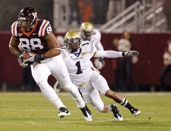 BLACKSBURG, VA - NOVEMBER 04: Tight end Andre Smith #88 of the Virginia Tech Hokies runs with the ball past safety Isaiah Johnson #1 of the Georgia Tech Yellow Jackets at Lane Stadium on November 4, 2010 in Blacksburg, Virginia.  (Photo by Geoff Burke/Get