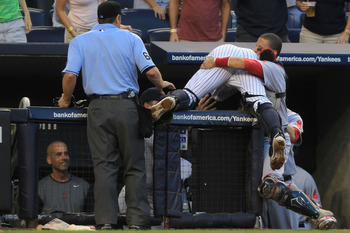 NEW YORK - SEPTEMBER 25:  Francisco Cervelli #29 of the New York Yankees is helped by Victor Martinez #41 of the Boston Red Sox after falling over the Red Sox dugout wall trying to catch a foul ball during their game on September 25, 2010 at Yankee Stadiu