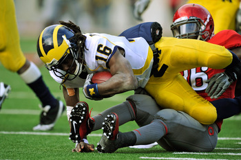 COLUMBUS, OH - NOVEMBER 27:  Quarterback Denard Robinson #16 of the Michigan Wolverines is sacked for a loss by Brian Rolle #36 of the Ohio State Buckeyes at Ohio Stadium on November 27, 2010 in Columbus, Ohio.  (Photo by Jamie Sabau/Getty Images)