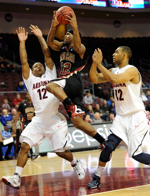 LAS VEGAS - NOVEMBER 26:   Robert Smith #12 of the Santa Clara Broncos drives between Lamont Jones #12 and Jamelle Horne #42 of the Arizona Wildcats during the third round of the Las Vegas Invitational at The Orleans Arena November 26, 2010 in Las Vegas,
