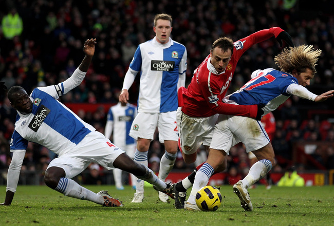 MANCHESTER, ENGLAND - NOVEMBER 27:  Dimitar Berbatov of Manchester United is challenged by Michel Salgado and Chris Samba (L) of Blackburn Rovers during the Barclays Premier League match between Manchester United and Blackburn Rovers at Old Trafford on No